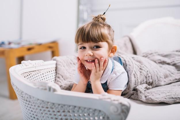 Bambina felice che si trova sul divano sotto coperta