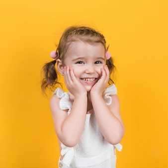 Bambina felice che sorride sulla priorità bassa gialla