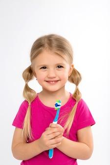 Bambina felice che sta con lo spazzolino da denti isolato su bianco.