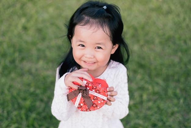 Bambina felice che tiene in mano un contenitore di regalo a forma di cuore