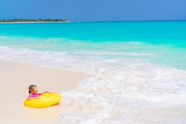 Bambina felice con il cerchio di gomma gonfiabile divertendosi sulla spiaggia in yhe acque basse