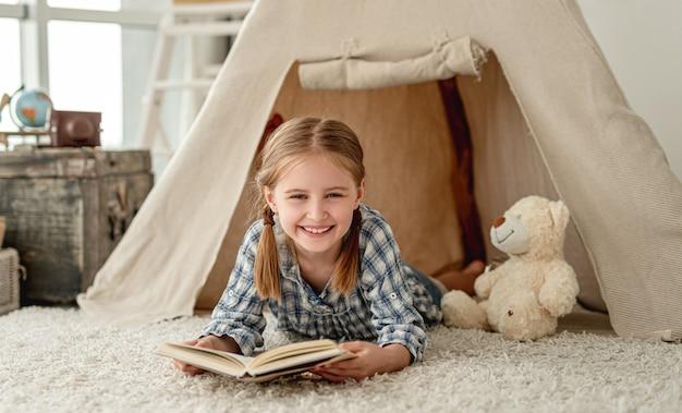 Bambina felice con il libro in wigwam