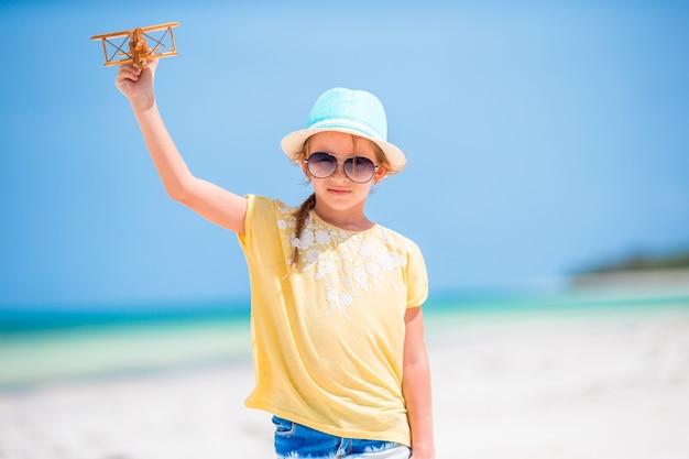 Bambina felice con l'aeroplano giocattolo in mani sulla spiaggia bianca