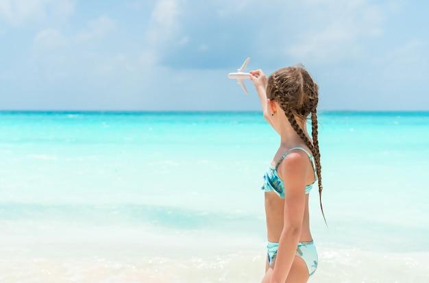 Bambina felice con l'aeroplano giocattolo in mani sulla spiaggia di sabbia bianca.