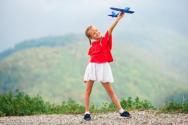 Bambina felice con l'aeroplano giocattolo nelle mani in montagna