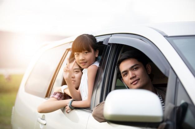 Bambina felice con la famiglia asiatica che si siede in macchina
