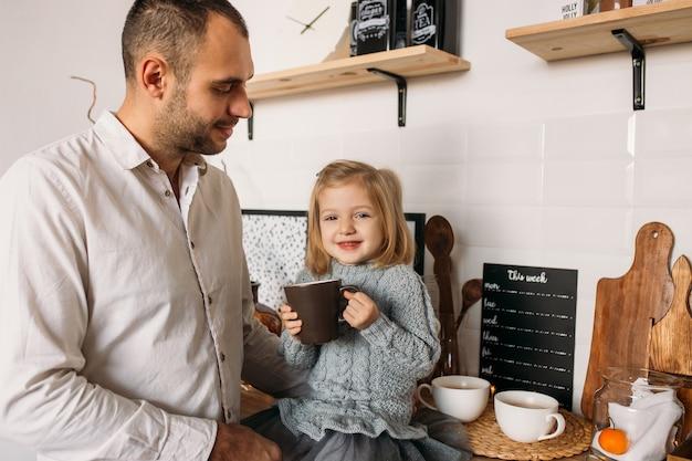 Bambina felice con una tazza di tè.