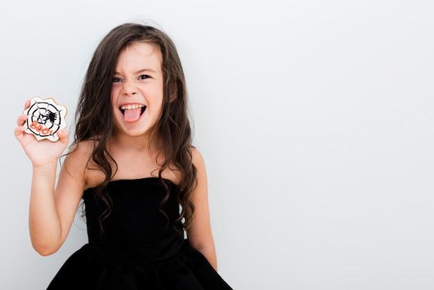 Bambina felice di vista frontale che mangia un biscotto