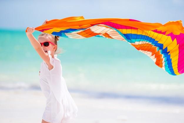 Bambina felice divertendosi in esecuzione con il pareo sulla spiaggia bianca tropicale