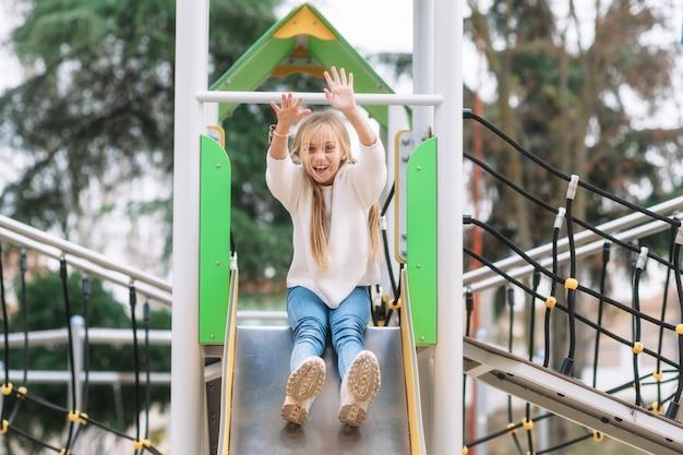 Bambina felice divertirsi sulla diapositiva nel parco.