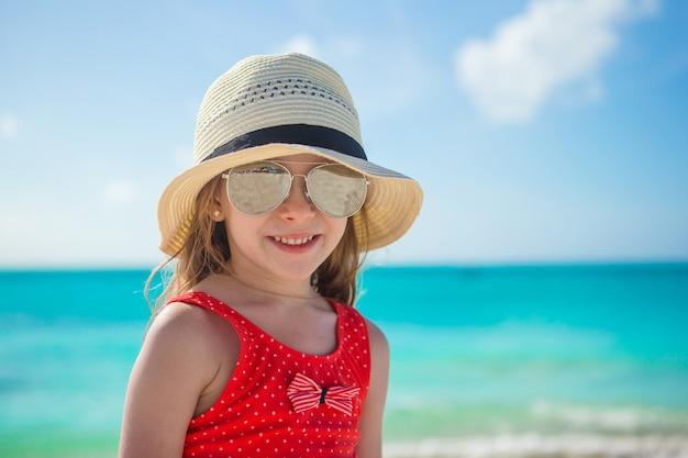Bambina felice in cappello sulla spiaggia durante le vacanze estive