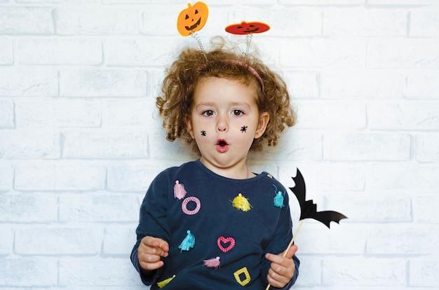 Bambina felice in costume con zucche, con ragni dipinti sulle guance, con in mano pipistrello e fischi spaventosi. bambini di halloween.