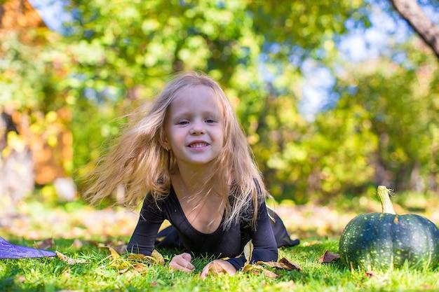 Bambina felice in costume di halloween con jack zucca. dolcetto o scherzetto