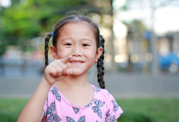 Bambina felice in giardino con indicare alla macchina fotografica.
