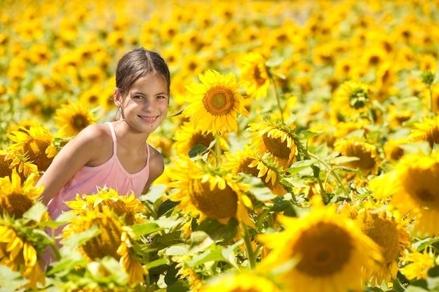 Bambina felice in un campo di girasoli