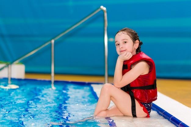 Bambina felice in un giubbotto rosso seduto sui gradini della piscina nel parco acquatico