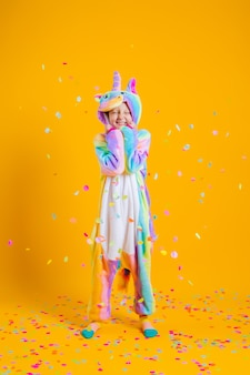 Bambina felice nell'unicorno di kigurumi che balla su una parete gialla fra i coriandoli multicolori