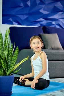 Bambina felice nella posa del loto che si siede sulla stuoia blu a casa, divertendosi.