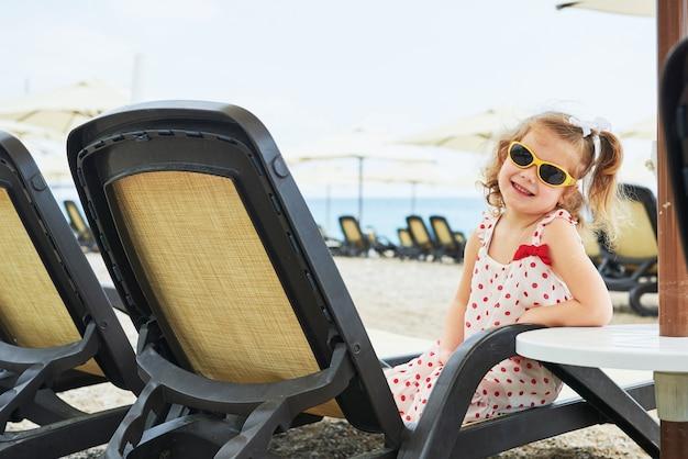 Bambina felice sui lettini in riva al mare
