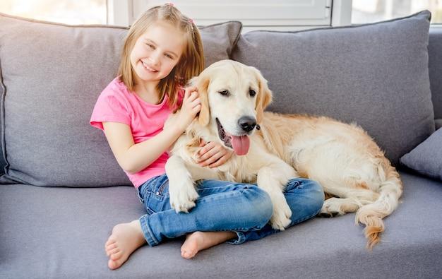 Bambina felice sul divano con il golden retriever nella stanza luminosa