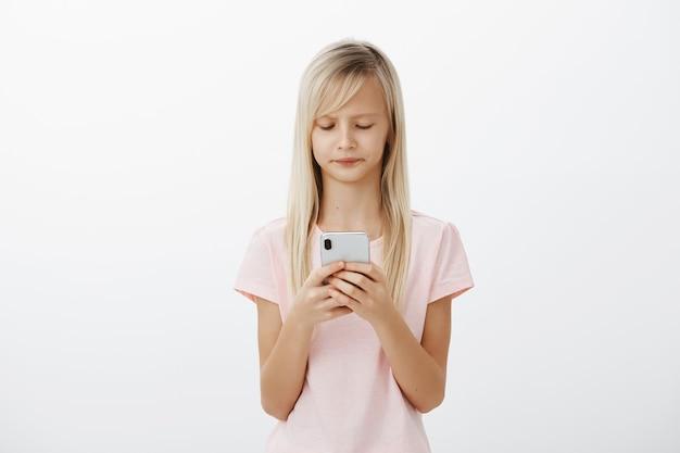Bambina frustrata scontenta con i capelli biondi in maglietta rosa casual, accigliata, guardando lo schermo dello smartphone, arrabbiata con un messaggio triste, in attesa del nuovo video del blogger preferito