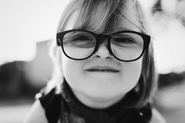 Bambina graziosa allegra con gli occhiali