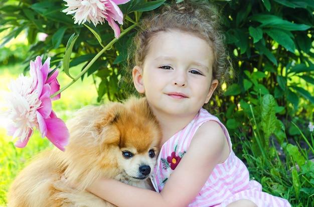 Bambina graziosa che abbraccia il suo spitz pomeranian