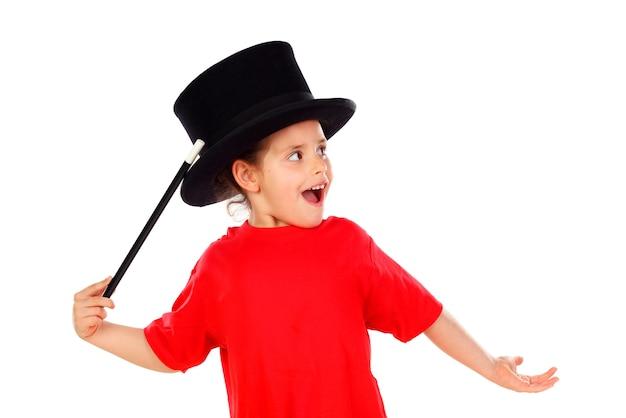 Bambina graziosa che fa magia con un cappello a cilindro e una bacchetta magica