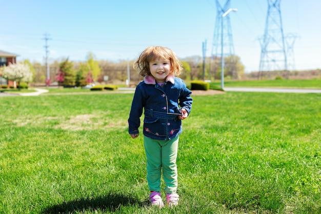 Bambina graziosa che gioca all'aperto in primavera