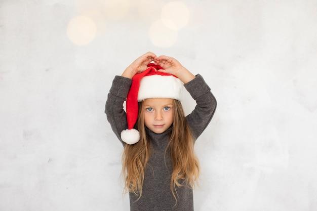 Bambina graziosa che porta un cappello del babbo natale