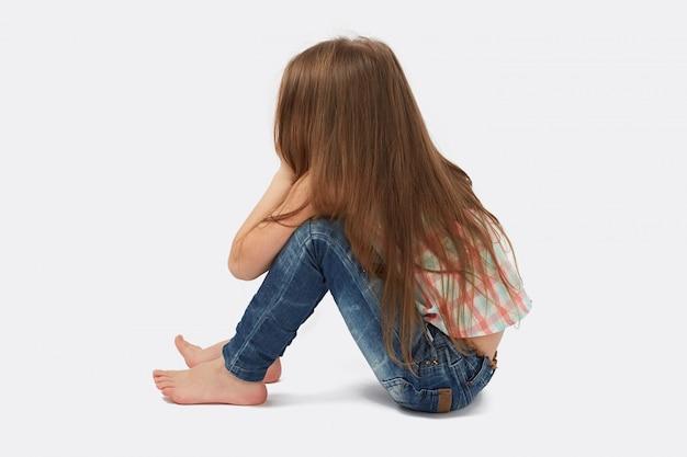 Bambina graziosa che si siede sul pavimento