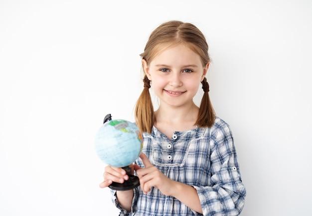 Bambina graziosa che tiene piccolo globo
