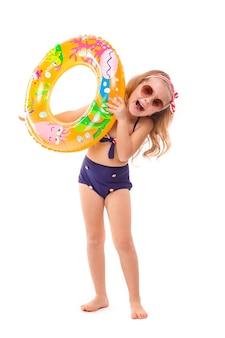 Bambina graziosa in bikini a strisce rosso, fondi blu, occhiali da sole e corona rosa