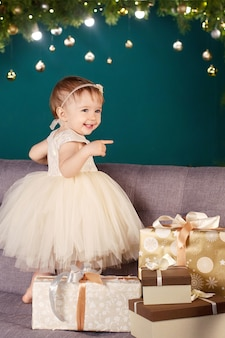 Bambina graziosa in vestito bianco che gioca e che è felice circa l'albero di natale e le luci.