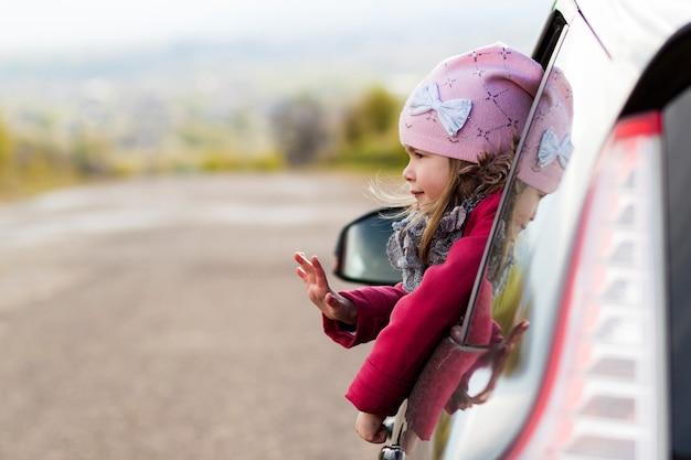 Bambina graziosa nell'automobile che osserva attraverso il finestrino della macchina.