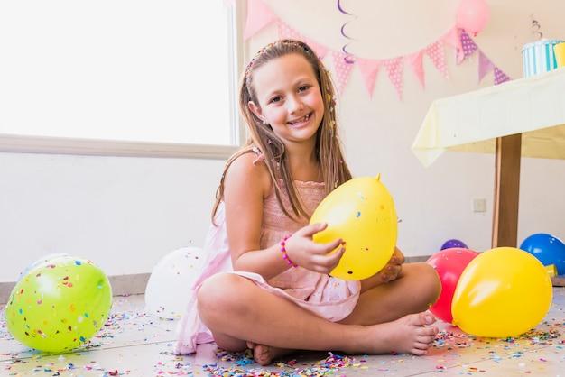 Bambina graziosa sorridente che si siede sul pavimento con i coriandoli e gli aerostati