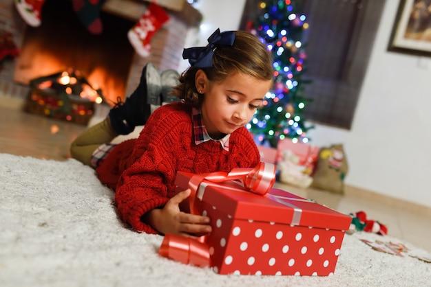 Bambina guardando un regalo rosso