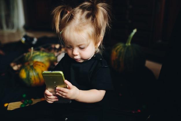 Bambina guardando un telefono intelligente con uno sfondo zucca