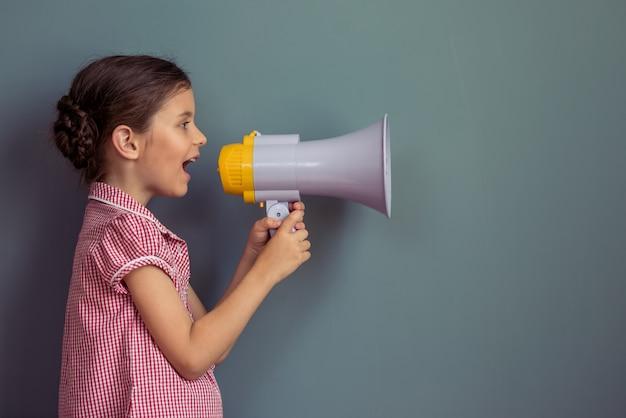 Bambina in abito carino urlando in un altoparlante