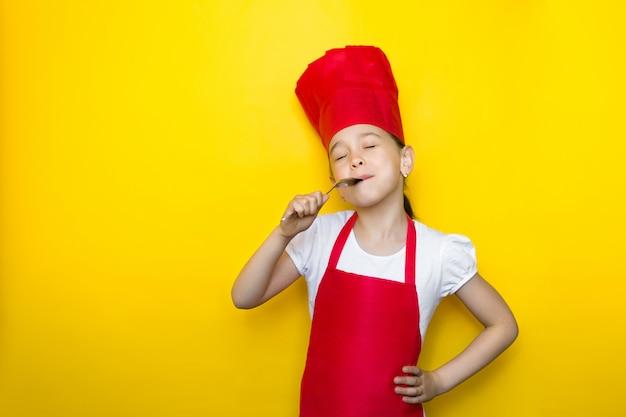 Bambina in abito da cuoco leccare il cucchiaio, chiudendo gli occhi, delizioso gusto sul giallo