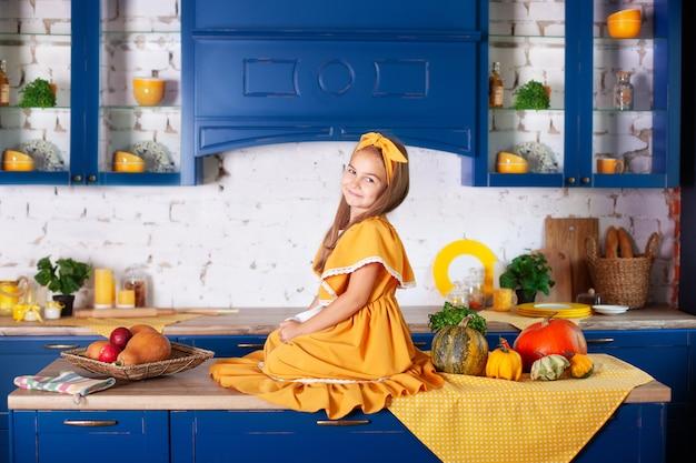 Bambina in abito giallo in autunno decor con zucche in cucina, vacanze di halloween. raccolta. sana alimentazione, vegetarismo, vitamine, verdure.