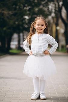 Bambina in abito nel parco