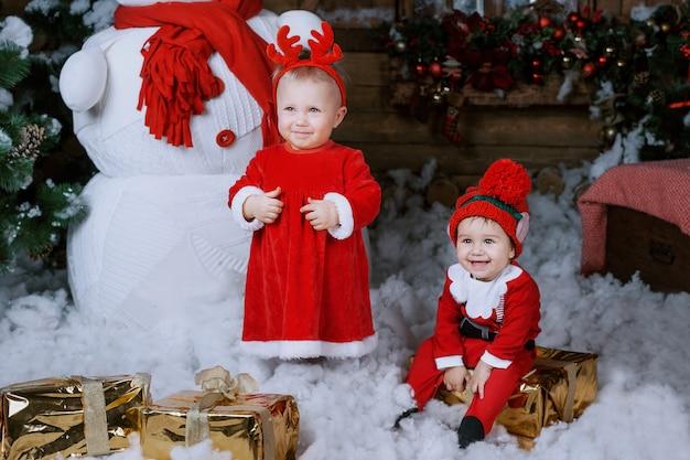 Bambina in abito rosso in un interno di casa in attesa di santa,