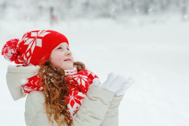 Bambina in berretto rosso cattura fiocchi di neve cadenti.