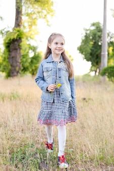 Bambina in campo verde durante la calda giornata estiva