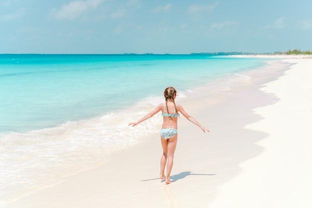 Bambina in cappello che cammina alla spiaggia durante la vacanza caraibica