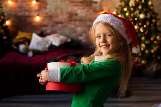 Bambina in cappello della santa che tiene un contenitore di regalo
