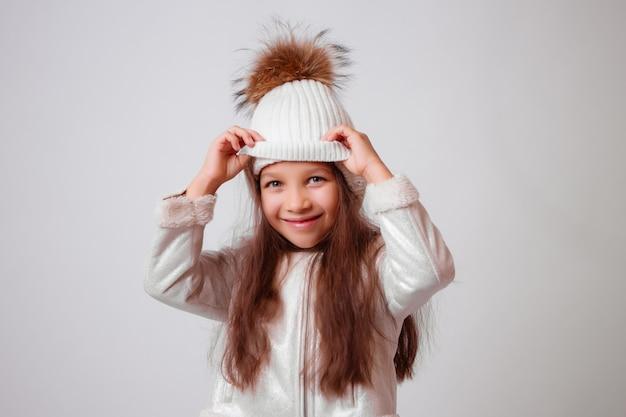 Bambina in cappello di inverno che sorride sul bianco