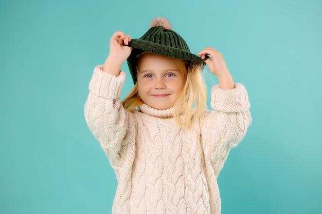 Bambina in cappello e maglione di inverno sull'azzurro