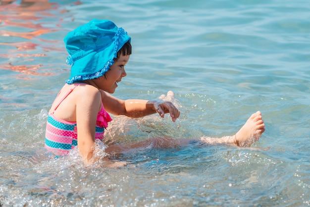 Bambina in costume da bagno che spruzza le gambe nel mare